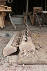 Using an auger to bore holes for the legs.  Note the bench is joined at an angle so the leg can be perpendicular to the bottom of the side but the legs will be splayed.